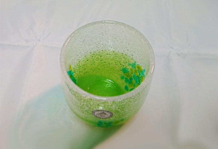 斜め<正規品>花見たる型(緑色)泡模様のたる型琉球ガラスに、綺麗な花びらをおよがせました。ベトナム製